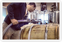 Worker filling a barrel at Elevation Brewing Company